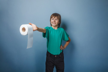 European-looking boy of ten years with toilet paper on a gray ba