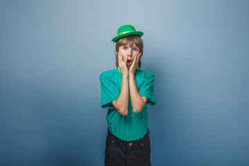 European appearance teenager boy in T-shirt with green hat put h