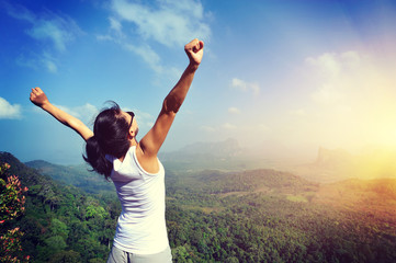 young woman cheering open arms at mountain peak