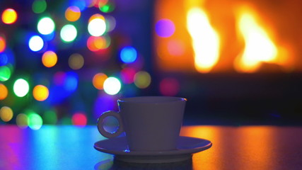 The cup of tea by fireplace and tree New Year background