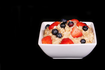Oatmeal with berries over black