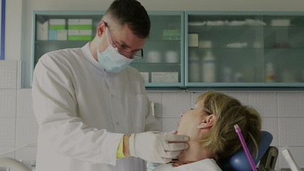 The dentist examines and treats a patient