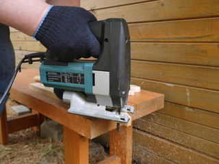 Man saws wooden plank
