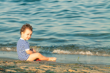 Playful toddler with sailor shirt sitting at the edge of the wav