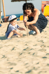 Sweet toddler dressed as a sailor sitting on a beach and playing