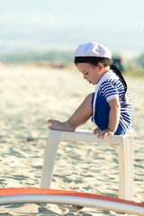 Sweet toddler dressed as a sailor sitting on a plastic table on