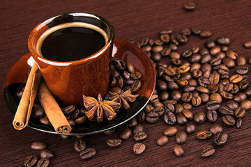 Coffee cup and beans on a wooden table. Dark background.