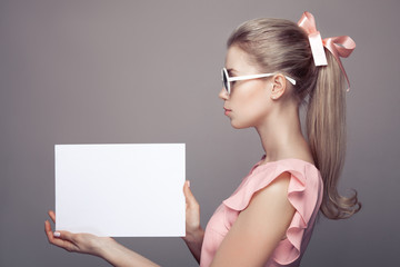 Fashion Woman With Sunglasses Holding Empty Paper Blank In Hands