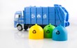 Colored trash bins and garbage truck toys on white background - 78685073