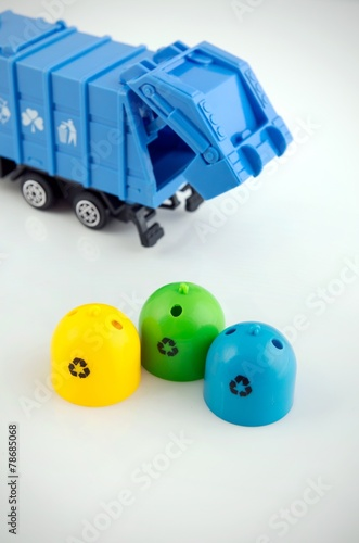 Colored trash bins and garbage truck toys on white background - 78685068
