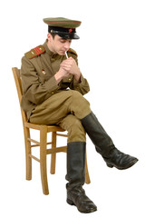 a young Soviet officer sitting in a chair smoking a cigarette
