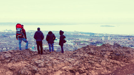Tourists enjoying view of Edinburgh from top of Arthurs seat