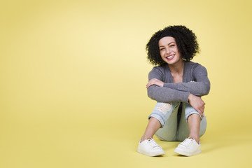 Happy girl sitting smiling on yellow background with copy space.