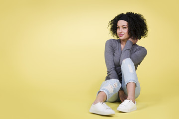 Young girl with sexy look sitting on isolated yellow background.