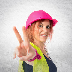 Worker woman doing victory gesture over white background