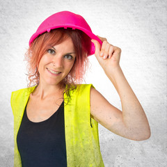 Woman worker with pink helmet over white background
