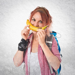 Girl making happy gesture with banan over isolated white backgro