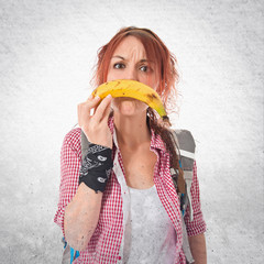 Girl making sad gesture with banan over isolated white backgroun