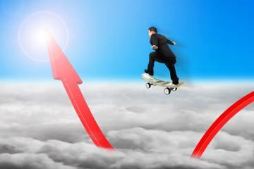 Businessman skateboarding on red arrow pointing up with sunlight