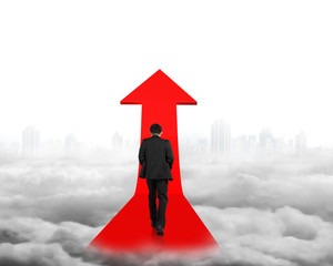 Businessman walking on red arrow sign path with cityscape clouds