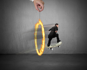 Businessman skating on money skateboard through fire circle
