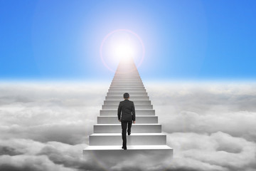 Businessman climbing the concrete stairs with blue sky sunlight