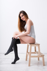 Happy woman sitting on the chair and dressing gaiters