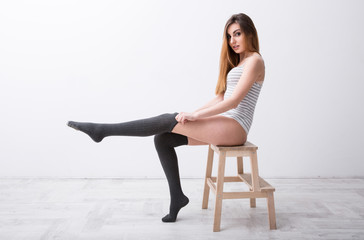 sexy woman sitting on the floor and looking at camera