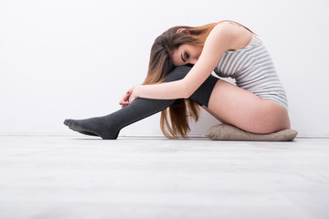 Side view portrait of a sexy woman sitting on the floor