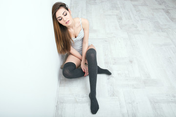 Sexy young woman sitting on the floor and leaning on the wall