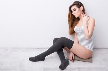 Portrait of a sexy young woman sitting on the wooden floor