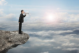Businessman using megaphone yelling on cliff with sunlight cloud