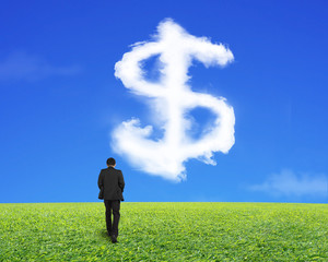 Rear view of businessman walking with dollar sign shape cloud