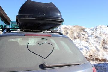 Winterurlaub: Ein Herz auf einer Autoscheibe im Skiurlaub