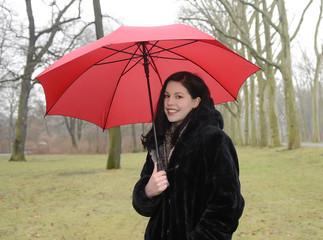 Fröhliche junge Frau mit Schirm im Park, Berlin, Deutschland