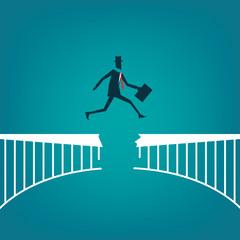 Businessman leaping over broken bridge