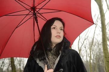 nachdenkliche junge Frau mit Schirm im Park, Berlin, Deutschland