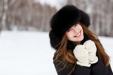 Portrait of happy young woman in luxury fur hat