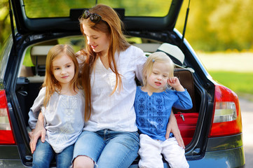 Two little sisters and their mother in a car