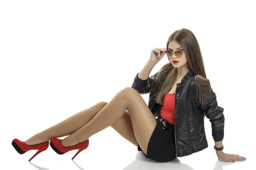 Sexy woman wearing leather jacket, shorts and red high heels
