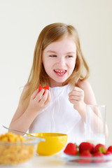 Adorable little girl eating cereal in a kitchen