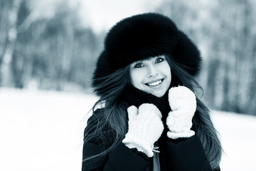 Portrait of beautiful smiling young woman in luxurious fur head