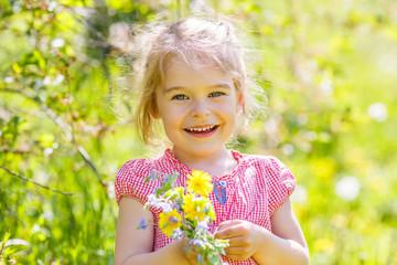 Happy little girl in spring sunny park