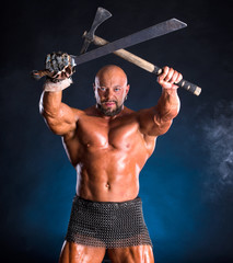 Handsome muscular ancient warrior with axe and sword