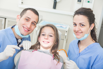 Dentist and dental assistant portrait with young patient