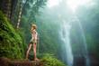 Female adventurer looking at waterfall - 78690812