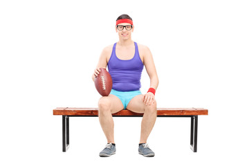 Male football player sitting on a bench