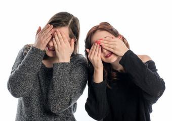 2 Mädchen halten sich die Augen zu