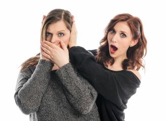 Mädchen hält Freundin die Ohren zu