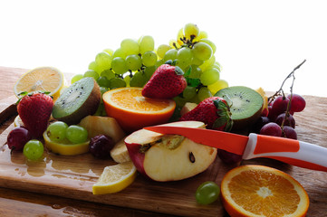 juicy fruits with knife on a wooden board